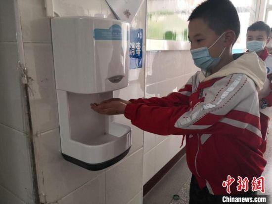 学生们进入教学楼后,快速地在大厅设置的电子洗手消毒装置前消毒。