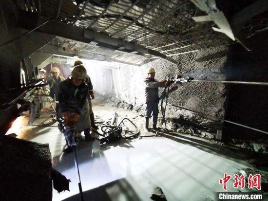 图为工人们在隧道内施工。
