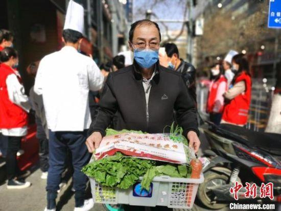图为爱心企业给志愿者分发蔬菜。