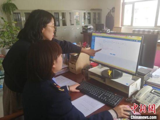 图为甘肃省市场监管局工作人员为企业办理动产抵押登记。(资料图)甘肃省市场监管局供图