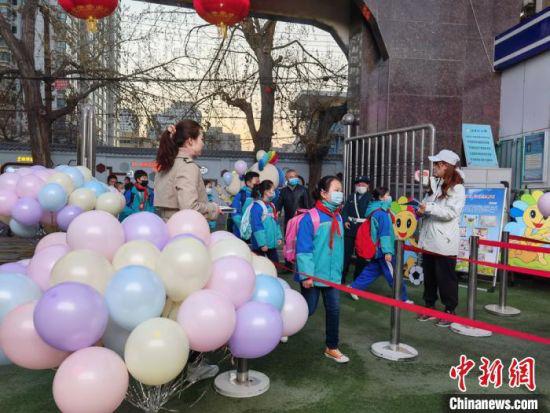 图为老师们在校门口布置气球、吉祥物欢迎学生归校。 刘玉桃 摄