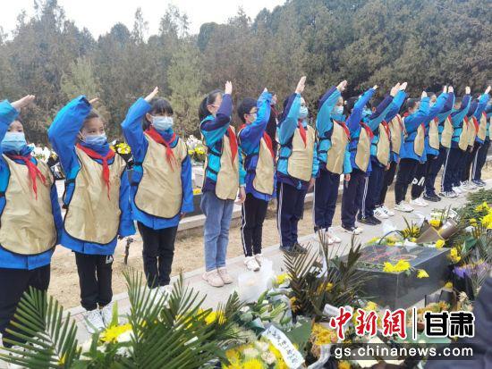 图为小学生向烈士敬队礼。