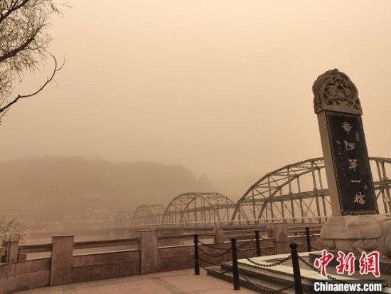 """图为笼罩在滚滚沙尘中的""""天下黄河第一桥""""兰州中山桥。 冯志军 摄"""