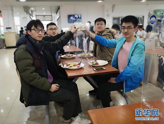 2月11日,东北大学大三学生曹澎骏(左二)和三位临时室友吃着学校准备的年夜饭。新华社记者 王莹摄