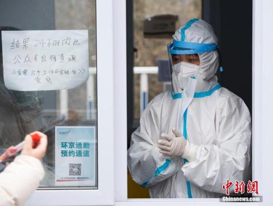 图为北京某核酸检测采样点的一名工作人员准备为市民进行采样。中新社记者 侯宇 摄