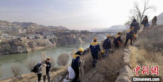 图为职工们携带检修、检测设备准备上桥。 魏建军 摄