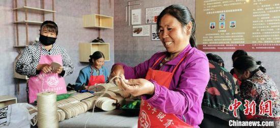"""图为立桥山村妇女在家门口""""就业""""纳鞋底。"""