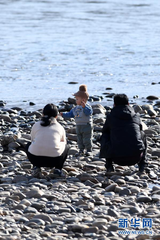 2月18日,市民带着孩子在黄河兰州段河床上游玩。新华社记者 范培珅 摄