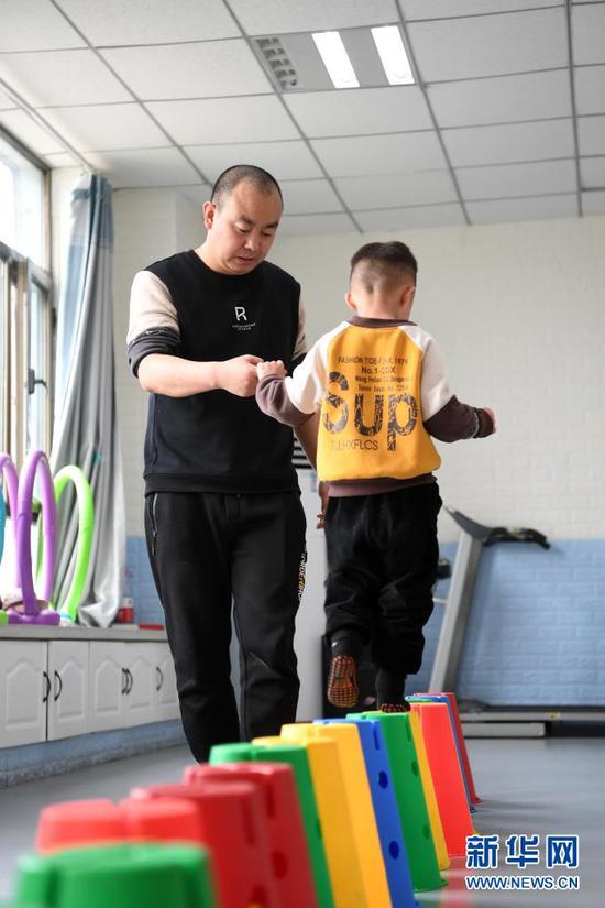 在兰州欣雨星儿童心理发展中心,丁强(左)引导孩子进行体能训练(3月30日摄)。新华社记者 范培珅 摄
