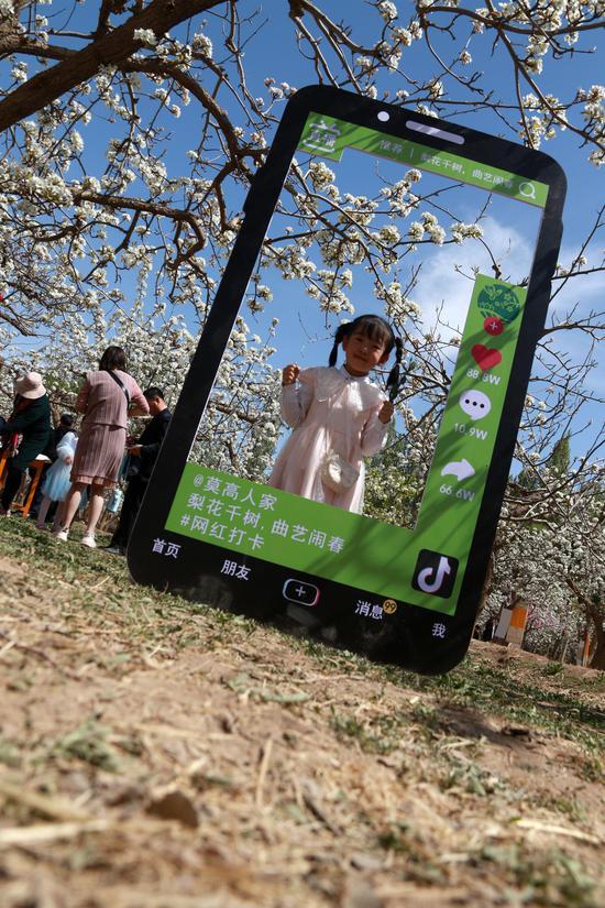 2021年4月17日,小朋友在甘肃省敦煌市莫高镇泾桥村梨园中拍照。