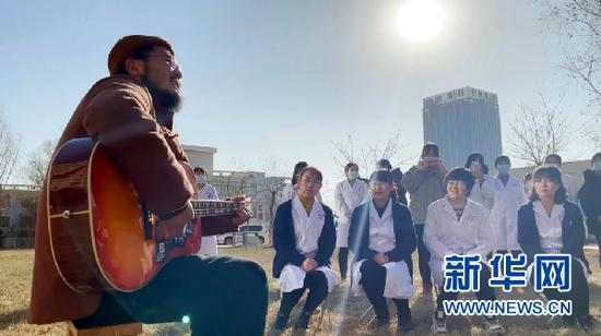 张尕怂(左一)为白银市中西医结合医院的医护人员代表演唱(新华社记者 程楠 摄)