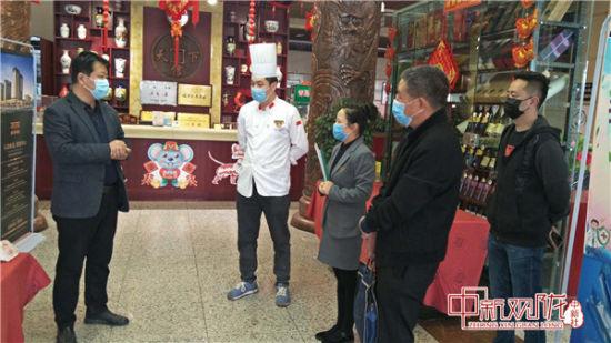 图为崆峒区监管人员督促餐饮服务单位推行使用公筷公勺。