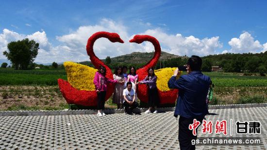 图为游客在王坪村景观带上,与天鹅造型饰品合影留念。