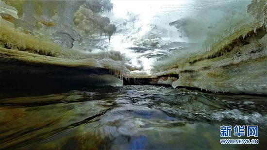 河水在冰盖下流动。新华网发(安维斌 摄)
