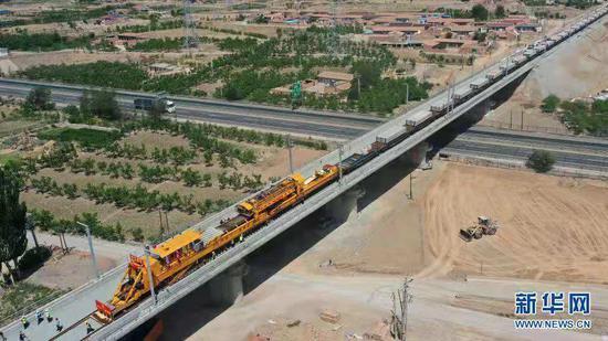 5月30日,中铁十一局建设者操作CPG500型铺轨机在中兰客专甘肃段新墩特大桥上进行铺轨作业(无人机照片)。 新华社记者 陈斌 摄