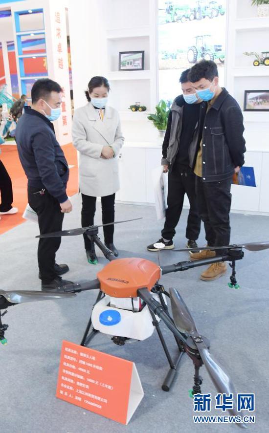 在临夏州举行的现代农业机械展示展销活动上,客商在了解植保无人机(3月12日摄)。新华社发(史有东 摄)