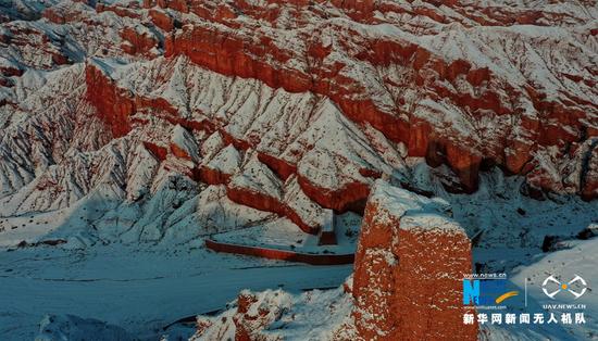 这是近日在甘肃省张掖市临泽县板桥镇航拍的红沟丹霞。雪后初晴,红沟丹霞披素纱,更显赤艳,成为冬日一道靓丽风景。新华网发(杨永伟 摄)