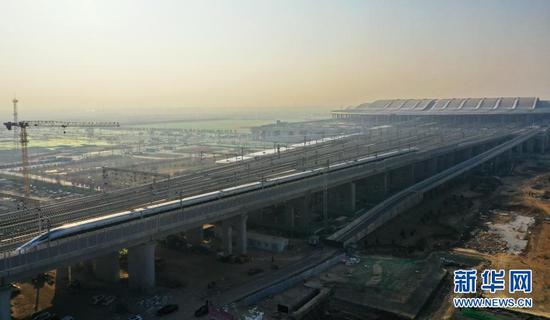 2020年12月27日,从雄安开往北京西的首发列车驶离雄安站(无人机照片)。当日,北京至雄安新区城际铁路大兴机场至雄安新区段开通运营,京雄城际铁路实现全线贯通,雄安站同步投入使用。新华社记者 牟宇 摄
