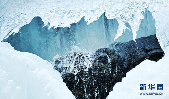 1月18日,在官鹅沟国家森林公园,冰瀑形成的冰挂与融化滴下的冰水组成奇特景观。新华社记者 陈斌 摄