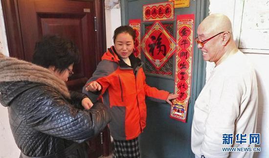 2月10日,社区工作人员为78岁的独居老人郭东辉贴春联。新华社记者 赵泳摄