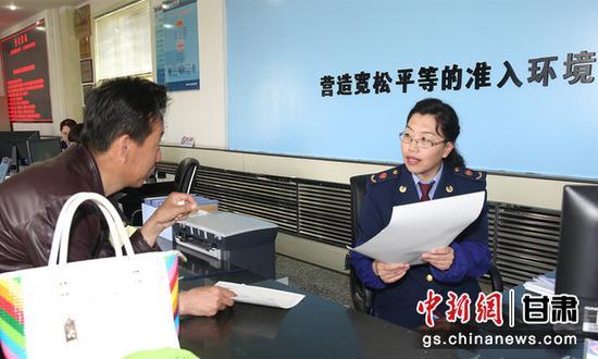 图为甘肃省市场监管局工作人员为民众讲解政策。