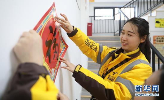 2月10日 ,美团专送骑手小月月在配送站点和同事贴福字。新华社记者 杨青摄