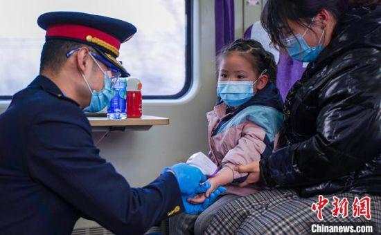 图为兰州客运段乘务人员为小旅客测温,做好旅客列车常态化疫情防控工作。 田多伟 摄