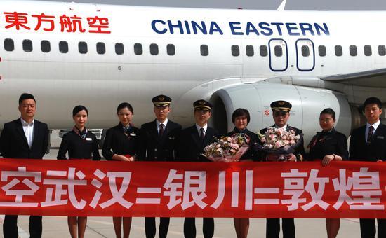 3月28日,在甘肃敦煌莫高国际机场,东航武汉--银川--敦煌首航航班机组人员与机场工作人员合影留念。