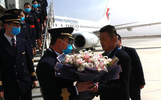 3月28日,在甘肃敦煌莫高国际机场,机场工作人员为东航武汉--银川--敦煌首航航班机组人员献花。