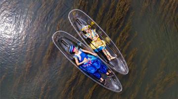 人在画中游!桂林少数民族青年乘透明船