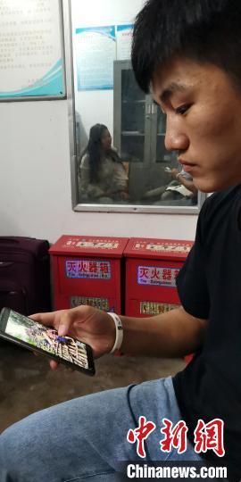蒙宣任在辨认新闻照片上的同伴。 蒋雪林 摄