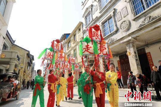 排灯表演队伍穿行在骑楼老街。 谭凯兴 摄