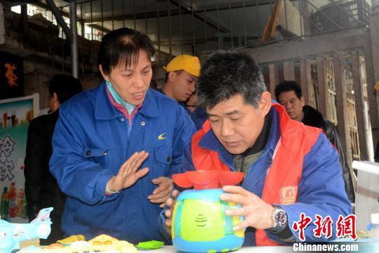 """3月2日,聋哑志愿者刘汉平的""""雷锋街市""""为市民免费修理电器。 孙赟飞 摄"""