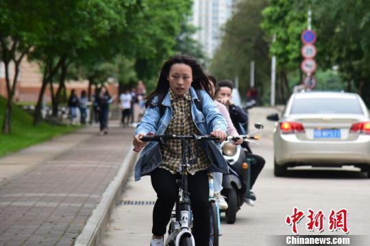 一名骑自行车上课的学生穿着长袖衬衫和牛仔外套。 王以照 摄