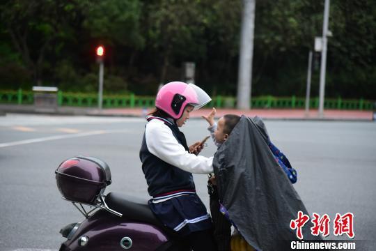 一位接孩子放学的市民穿着厚实的外套。 王以照 摄