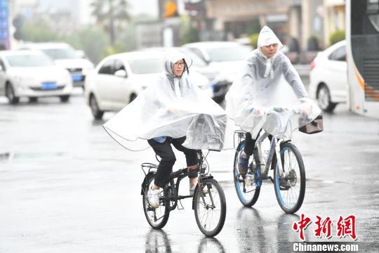资料图:民众在雨中出行。张浪 摄