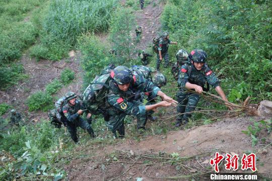 特战队员利用绳子攀爬斜坡。 李灿明 摄