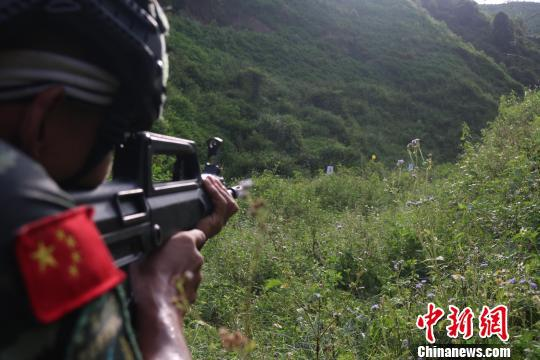 突击组对峡谷阵地左侧进行搜索射击。 李灿明 摄
