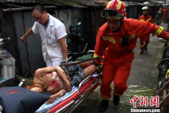图为消防官兵与医护人员一起将受伤女子抬到120救护车上。 焦晓佳 摄