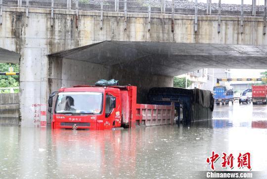 停放在涵洞中的货车,泡在水里。 朱柳融 摄
