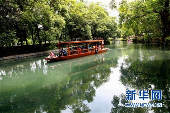 (游客在如画的广西桂林兴安县千年古灵渠中乘船游览。新华社发 王滋创摄)