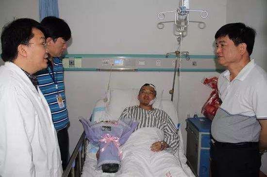 程文科(右)等领导看望慰问受伤民警韦春强。