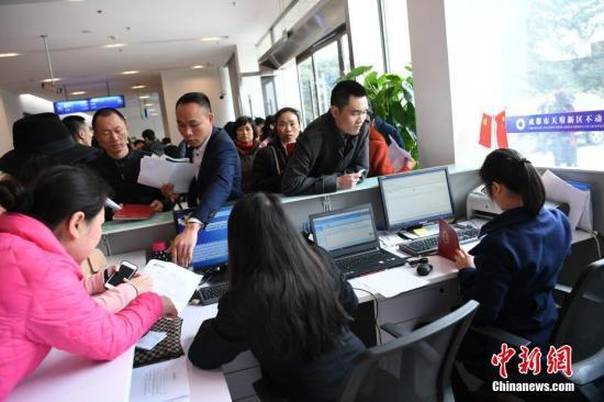资料图:不动产登记中心涌现大批购房者前来咨询新政策。 张浪 摄