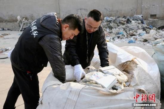 资料图:大连海关缉私警员查看洋垃圾。 中新社发 宋成明 摄