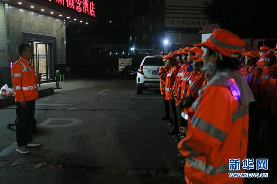 大年初一凌晨,南宁市西乡塘区环卫站华强片区队长陈色南(左)在布置当天的清扫任务。(2月5日拍摄)