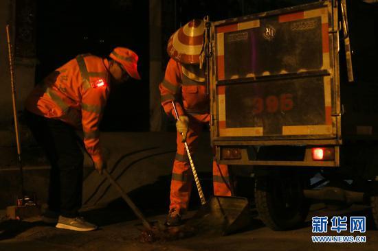 大年初一凌晨,南宁市西乡塘区华强片区环卫队队长陈色南(左)和工友在华兴里街道进行垃圾清扫工作。(2月5日拍摄)