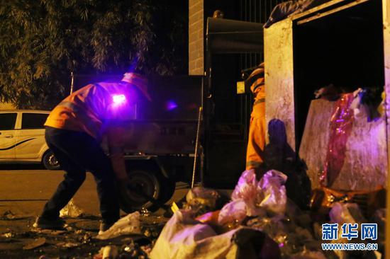 大年初一凌晨,南宁市西乡塘区环卫站华强片区队长陈色南(左)和工友在华兴里街道清理小区的垃圾屯放点。(2月5日拍摄)