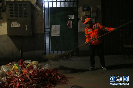 大年初一凌晨,南宁市西乡塘区环卫站华强片区队长陈色南在华兴里街道清理小区的垃圾。(2月5日拍摄)