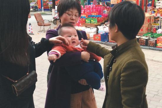 ▲大年初二,来参加聚会的表姑(右一)正在逗晚辈。新京报记者 周小琪 摄