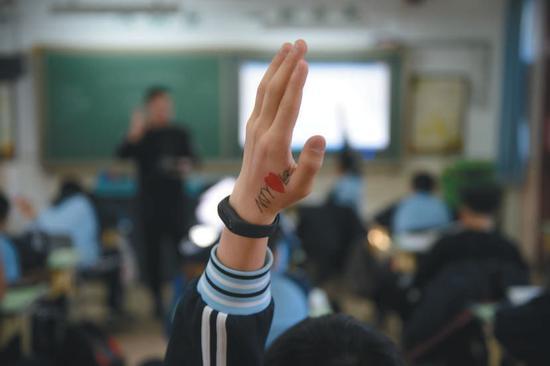 ▲2018年12月25日,北京市海淀寄读学校的学生在课堂上举手提问。 新京报记者 吴江 摄